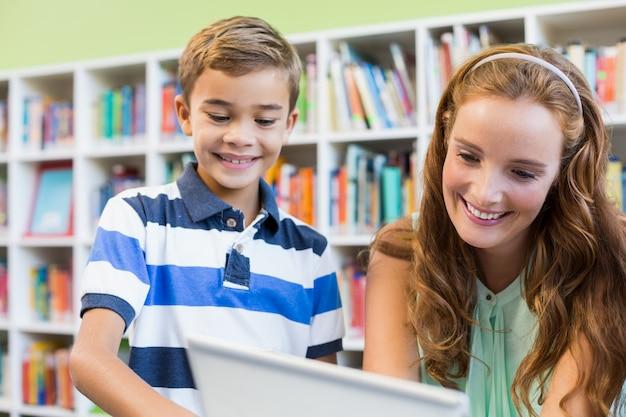 Enseignant, école, garçon, utilisation, ordinateur portable, bibliothèque