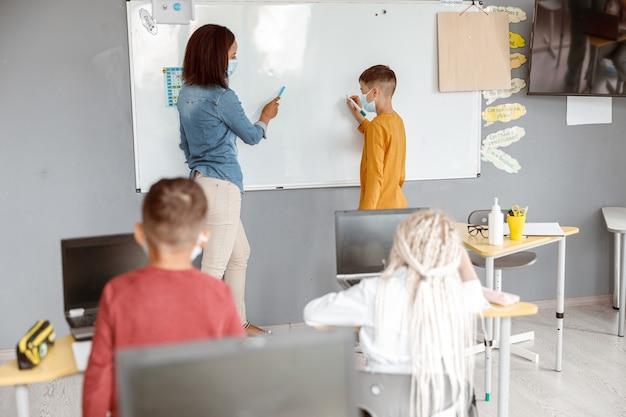 Enseignant et écolier debout près du tableau noir dans la salle de classe