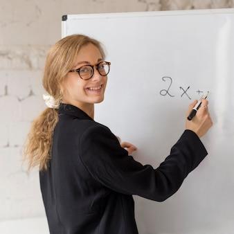 Enseignant écrit sur tableau blanc