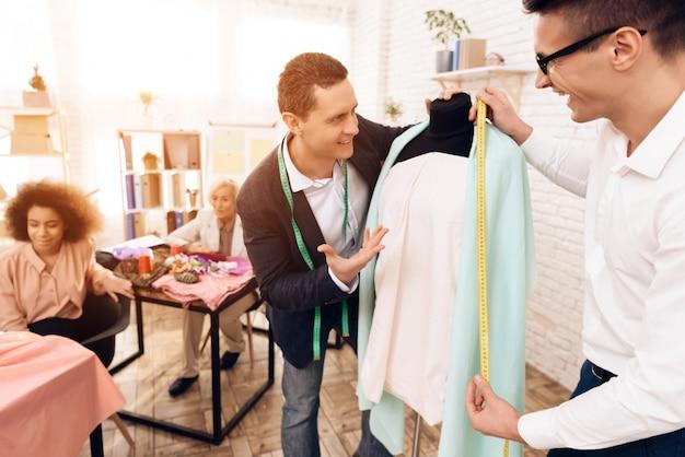 Enseignant et élève cherchent une nouvelle robe.