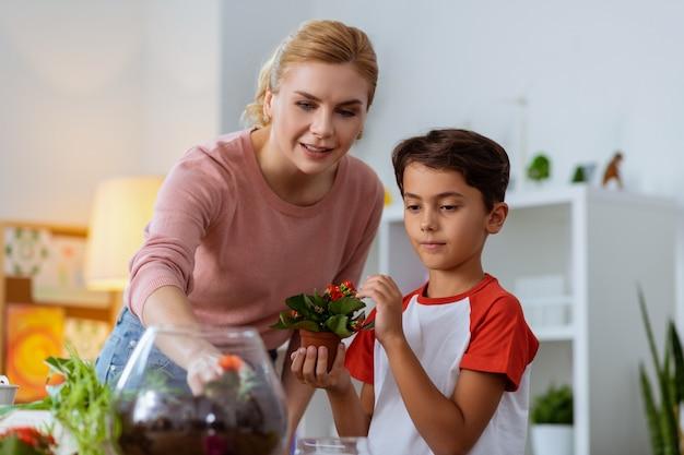 Enseignant et élève. élève mignon tenant un petit pot de fleurs avec des fleurs rouges debout près de son professeur intelligent