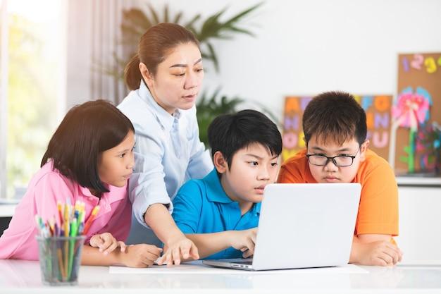 Enseignant et enfants asiatiques mignons utilisant l'ordinateur portable ensemble.
