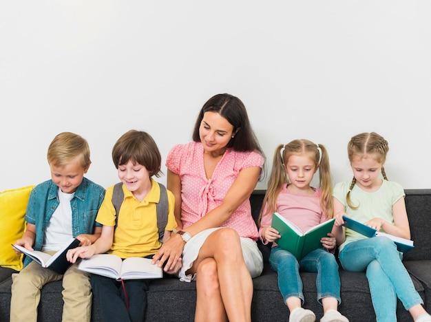 Enseignant et enfants assis ensemble