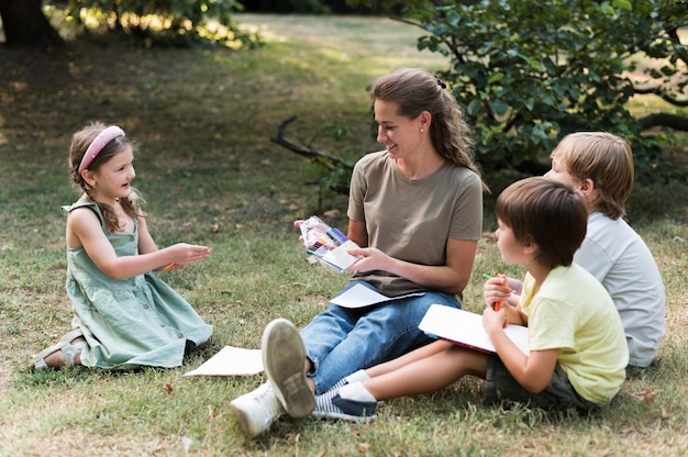 Enseignant et enfants assis sur l'herbe