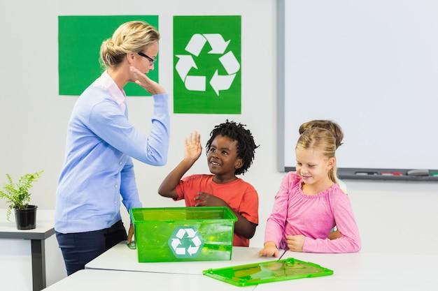 Enseignant et enfants donnant cinq aux enfants