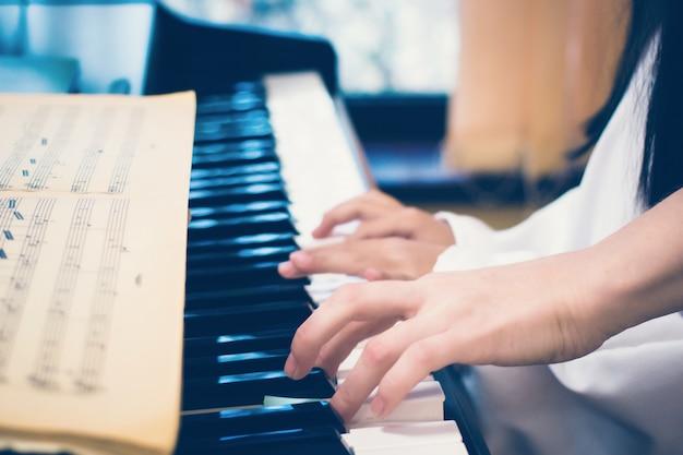 Enseignant enseignant à une petite fille à jouer du pianopiano clavier et mains d'enfant et d'adulte