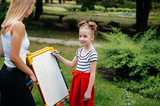 Un enseignant enseigne à une classe d'enfants dans un parc extérieur. retour à l'école, apprentissage pendant la pandémie.
