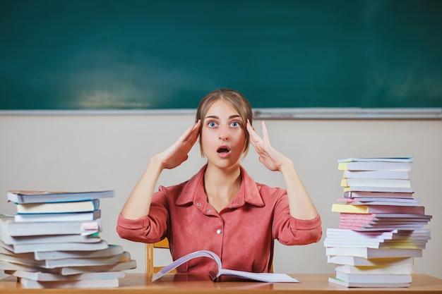 Enseignant entouré de livres assis dans la salle de classe.