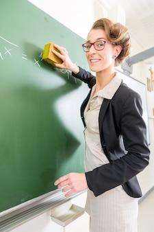 Enseignant avec une éponge devant une classe d'école
