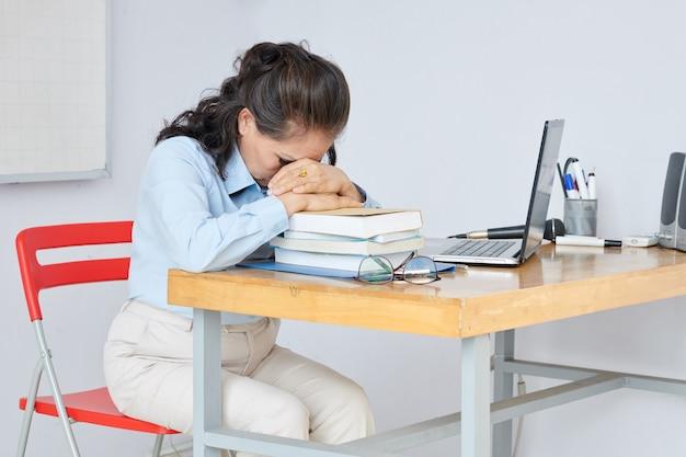 Enseignant épuisé s'appuyant sur la pile de livres d'étudiants sur son bureau pour se reposer après une longue journée stressante