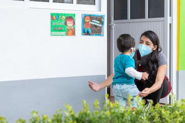 Enseignant étreignant un enfant de retour à l'école portant un masque facial après la pandémie de coronavirus