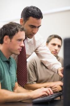 Enseignant et étudiant adulte en salle informatique