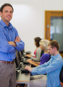 Enseignant avec des étudiants utilisant des ordinateurs dans la salle informatique