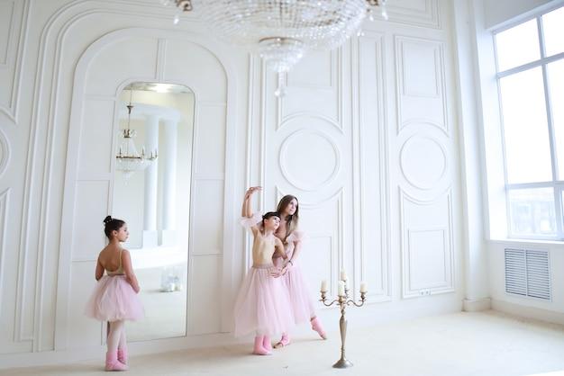 L'enseignant forme des mouvements de ballet avec des petites filles vêtues de vêtements roses dans la pièce