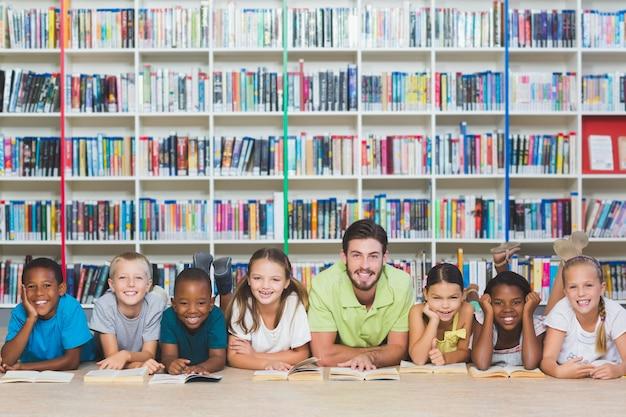 Enseignant, gosses, mensonge, plancher, utilisation, tablette numérique, dans, bibliothèque