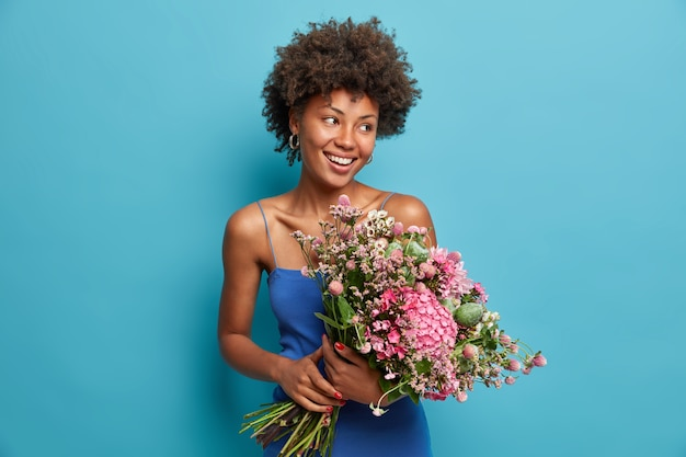 Un enseignant heureux pose avec un grand beau bouquet de fleurs reçu des élèves, regarde volontiers de côté, adore l'arôme frais et agréable, apprécie le parfum préféré, porte une robe bleue, se tient à l'intérieur.