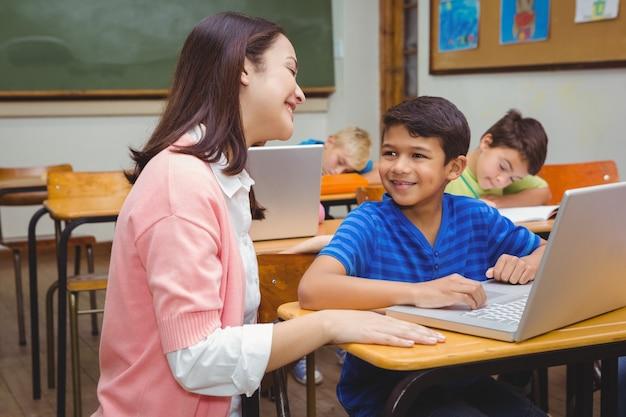 Enseignant heureux en utilisant un ordinateur portable avec un étudiant