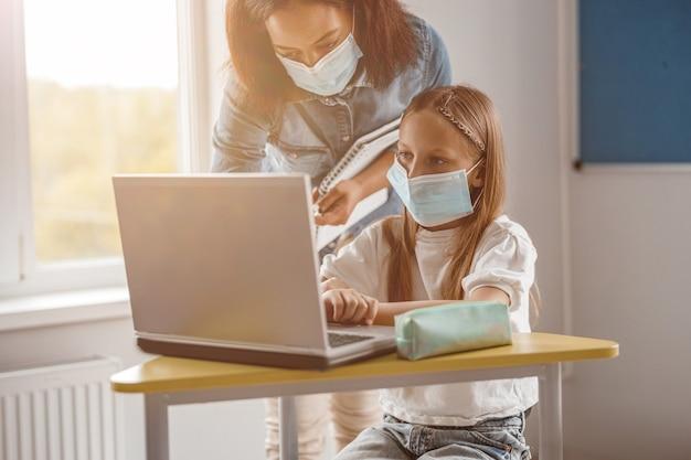 Enseignant et jeune écolière utilisant un ordinateur portable en classe