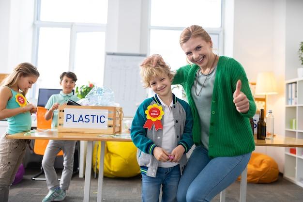 Enseignant joyeux. enseignant aux cheveux blonds joyeux étreignant son élève mignon après lui avoir donné une récompense