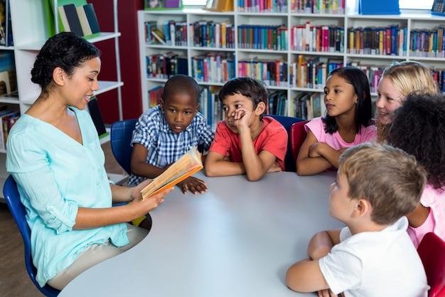 Enseignant lisant un livre aux enfants