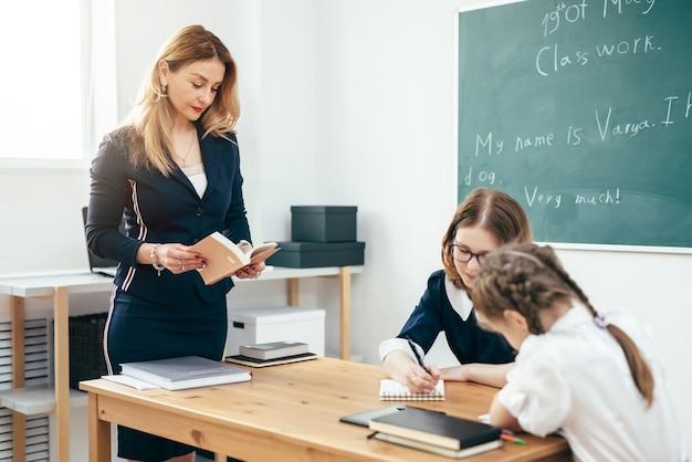 Enseignant avec livre donnant une leçon en classe.