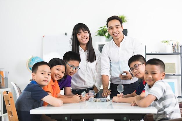 Un enseignant mâle gai expliquant quelque chose à un groupe de jeunes étudiants