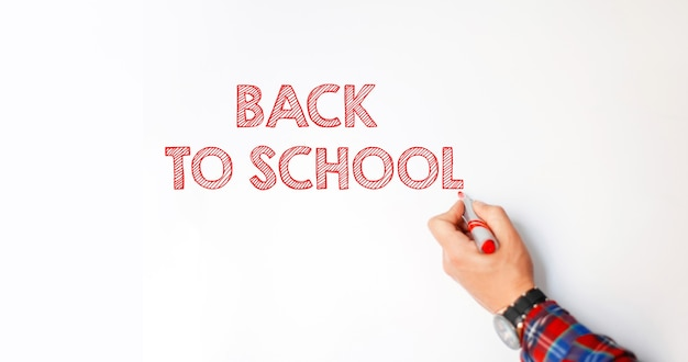 Un enseignant avec un marqueur rouge à la main écrit sur le tableau blanc le texte : retour à l'école. le début de l'année scolaire
