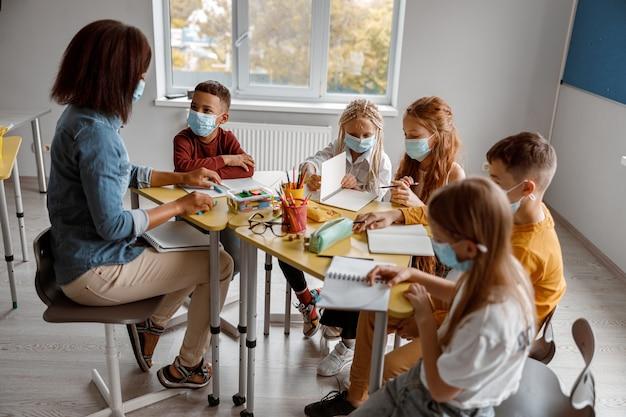 Enseignant en masque expliquant aux écoliers pendant une leçon à l'école