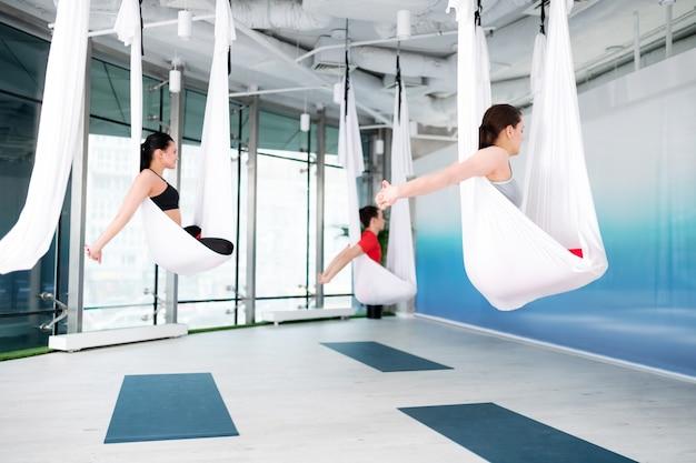 Enseignant montrant des poses. professeur de yoga professionnel aux cheveux noirs montrant de belles poses pour le yoga aérien