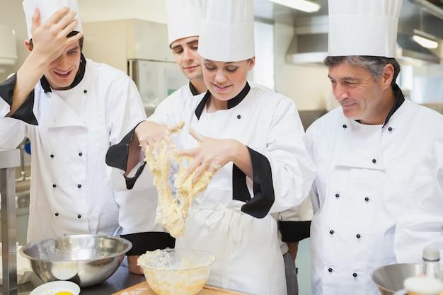Enseignant montrant à ses élèves comment mélanger la pâte