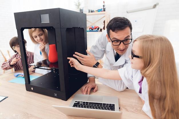 L'enseignant montre aux enfants le fonctionnement de l'imprimante 3d.