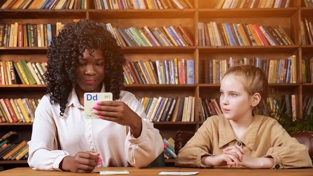 Un enseignant noir professionnel répète des lettres avec une jeune femme montrant des cartes mémoire contre des supports en bois marron avec des livres à la maison verrouillage covid, lumière du soleil