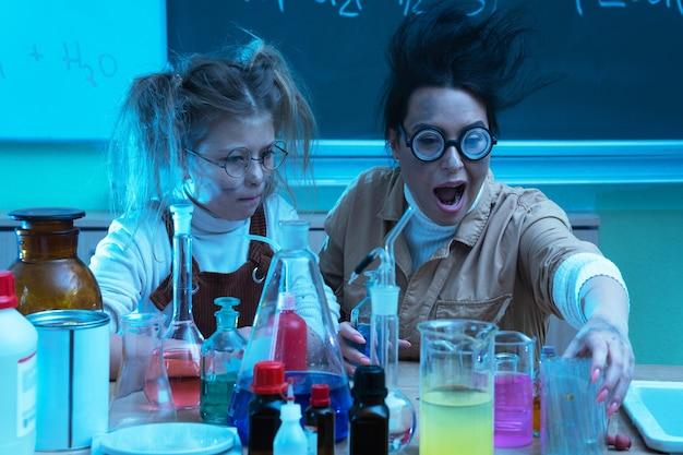 Enseignant et petite fille pendant la leçon de chimie mélangeant des produits chimiques