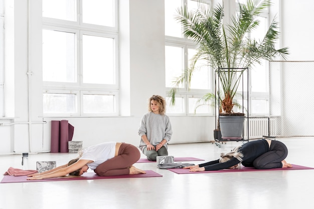 Enseignant plein coup en regardant les femmes faire du yoga