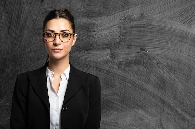 Enseignant portant des lunettes et debout dans la police d'un tableau noir de classe