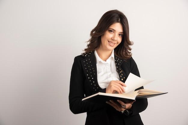 Enseignant positif posant avec un cahier ouvert.