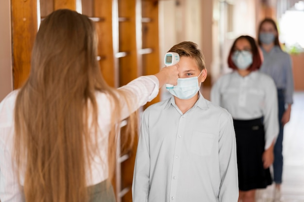 Enseignant prenant la température corporelle à l'école