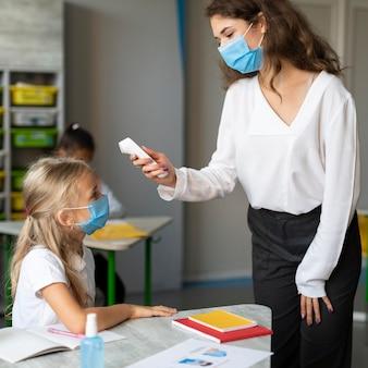 Enseignant prenant la température d'une petite fille