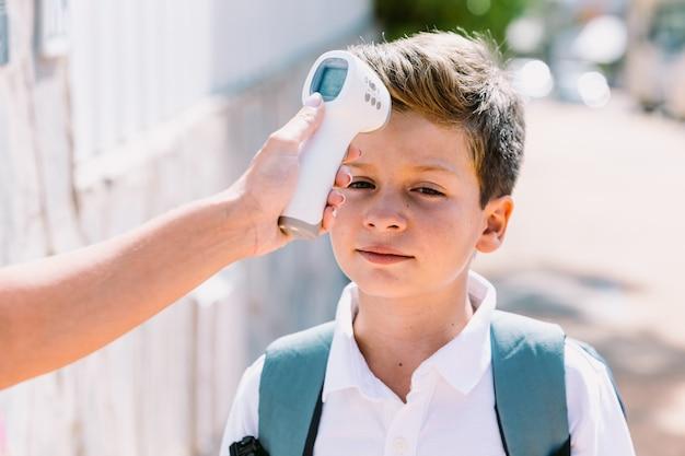 L'enseignant prend la température d'un enfant lorsqu'il entre à l'école avec un thermomètre électronique. concept de covid-19 et de pandémie de virus