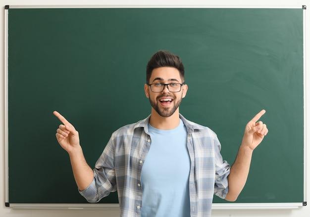 Enseignant près du tableau noir en classe