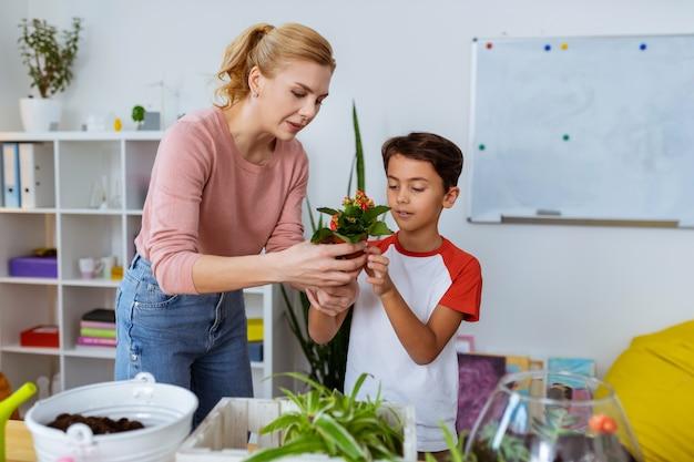 Enseignant serviable. professeur d'écologie aux cheveux blonds serviable aidant son élève à planter des fleurs