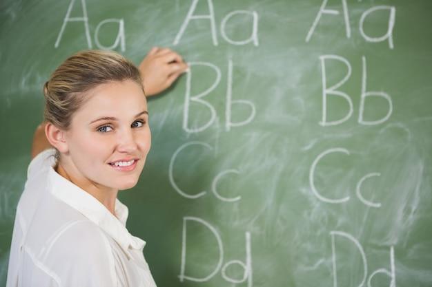 Enseignant souriant enseignant sur tableau noir en classe