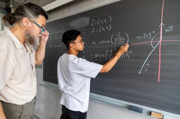 Un enseignant supervise un lycéen asiatique écrivant un exercice de mathématiques sur un tableau noir