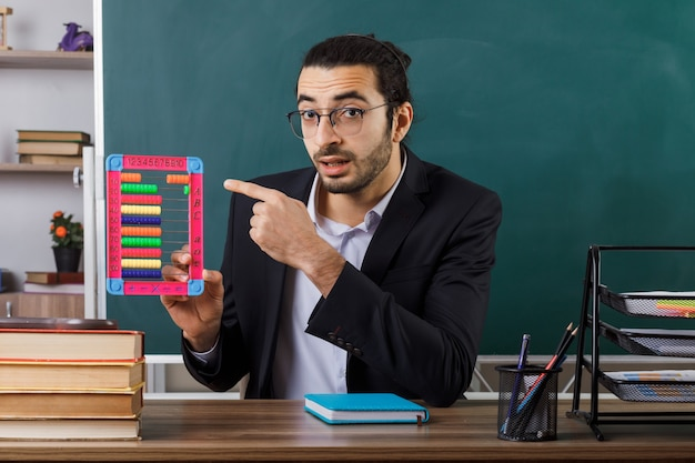 Enseignant surpris portant des lunettes tenant et pointant sur un boulier assis à table avec des outils scolaires en classe