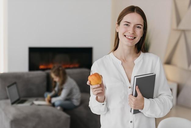 Enseignant tenant une pomme et enfant ayant cours virtuel