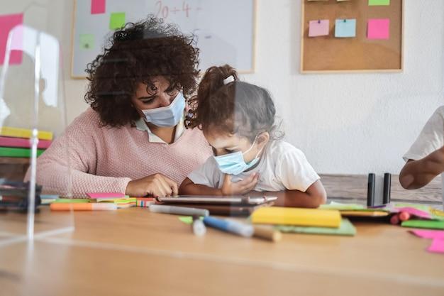Enseignant utilisant une tablette avec des enfants à l'école maternelle pendant une épidémie de coronavirus - focus sur la main de la femme