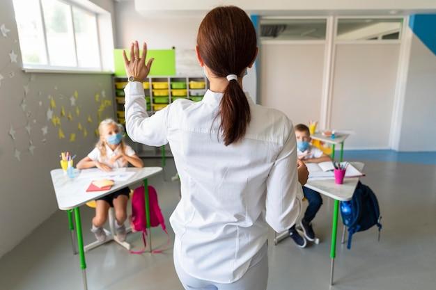 Enseignant de vue arrière en attente d'une réponse en classe
