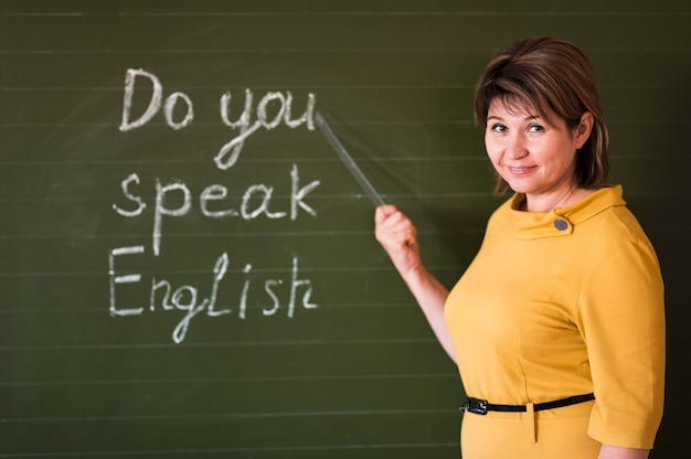 Enseignant de vue de face écrit au tableau