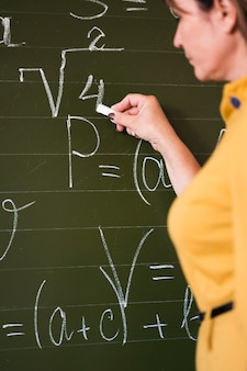 Enseignant de vue latérale écrit sur tableau noir