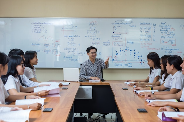 Une enseignante asiatique donne une leçon à un groupe d'étudiants dans une salle de classe
